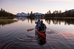 Canoeists at Nuk Tessli Wilderness Experience with view of the Coast Mountains, Whitton Lake, BC.