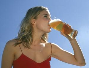 Junge Frau vor blauem Himmel mit Bier